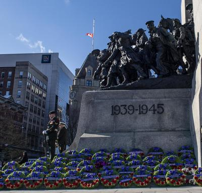 Hundreds of wreaths are laid at the base of the National War Memorial.  Two sentries stand at attention.