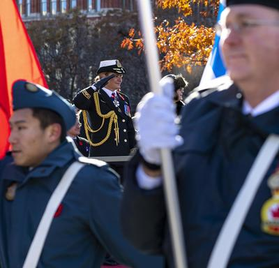 Servicemen holding flags are marching in the foreground.  Between their ranks we see the Governor General saluting as well as Ms. Anita Cenerini.