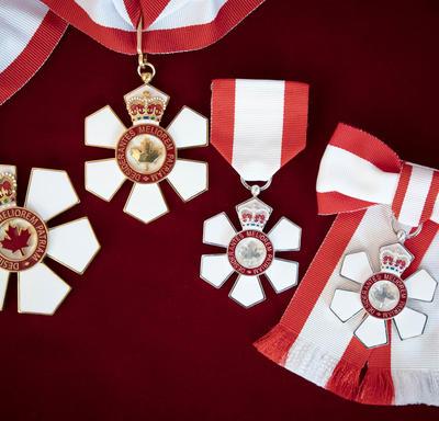 Quatre médailles représentant les trois niveaux de l'Ordre du Canada sont représentées sur un fond de velours rouge.