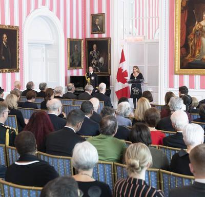 La gouverneure générale, Julie Payette, se tient à un podium et prononce un discours devant une foule assise d'environ 200 personnes.