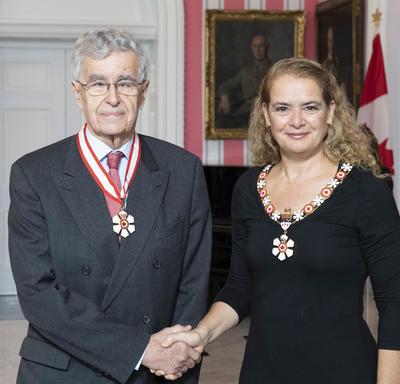 La gouverneure générale, Julie Payette, se tient debout aux côtés de Louis Lebel.  Tous deux portent l'insigne de l'Ordre du Canada.