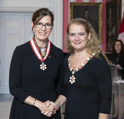 La gouverneure générale, Julie Payette, se tient debout aux côtés de Sophie D'Amours.  Tous deux portent l'insigne de l'Ordre du Canada.