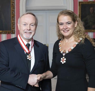 The Governor General, Julie Payette, stands next to Terence Matthews.  Both are wearing their Order of Canada insignias.