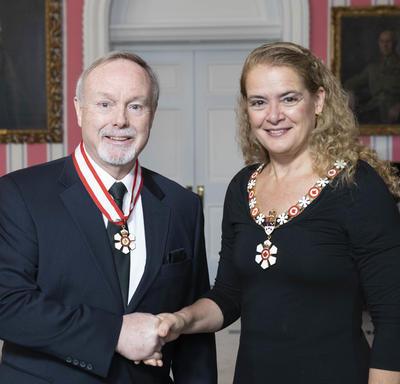 La gouverneure générale, Julie Payette, se tient debout aux côtés de Terence Matthews.  Tous deux portent l'insigne de l'Ordre du Canada.