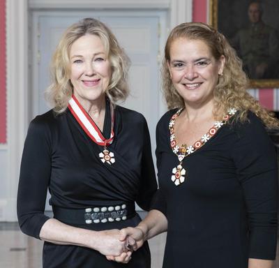 La gouverneure générale, Julie Payette, se tient debout aux côtés de Catherine O'Hara.  Tous deux portent l'insigne de l'Ordre du Canada.
