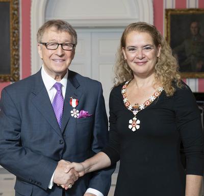 La gouverneure générale, Julie Payette, se tient debout aux côtés de Allan Andrews.  Tous deux portent l'insigne de l'Ordre du Canada.