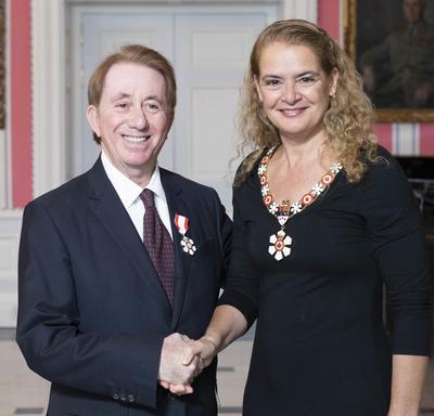La gouverneure générale, Julie Payette, se tient debout aux côtés de Mark Breslin.  Tous deux portent l'insigne de l'Ordre du Canada.