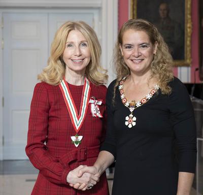 La gouverneure générale, Julie Payette, se tient debout aux côtés de Lynn Factor.  Tous deux portent l'insigne de l'Ordre du Canada.
