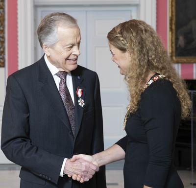 La gouverneure générale, Julie Payette, se tient debout à côté de Howard Gimbel. Ils se serrent la main. Tous deux portent l'insigne de l'Ordre du Canada.