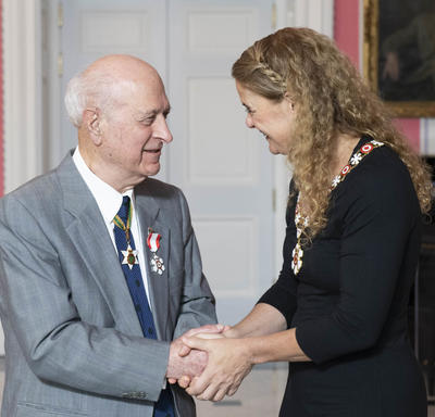 The Governor General, Julie Payette, shakes Kay Nasser's hand as they speak.  Both are wearing their Order of Canada insignias.