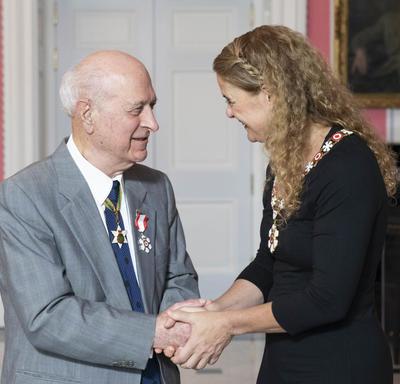 La gouverneure générale, Julie Payette, se tient debout à côté de Kay Nasser. Ils se serrent la main. Tous deux portent l'insigne de l'Ordre du Canada.