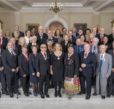 La Gouverneure générale, Julie Payette, est entourée de 41 récipiendaires de l'Ordre du Canada.  Ils se tiennent debout dans l'escalier du foyer de Rideau Hall.