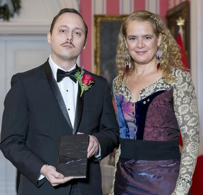 Michaël Trahan stands next to Governor General Julie Payette.  They hold a leather bound book and smile at camera.
