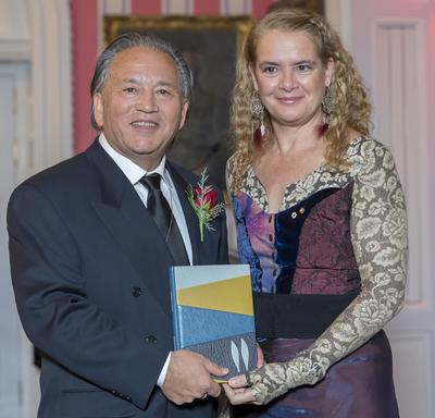 Darrel J. McLeod  stands next to Governor General Julie Payette.  They hold a leather bound book and smile at camera