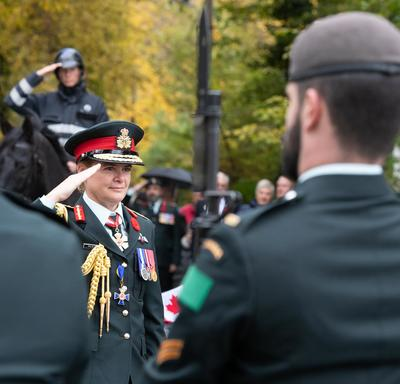 The Governor General Julie Payette, wearing an army uniform, salutes.  Servicemen and women stand in the foreground.