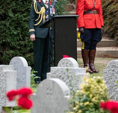 Governor General Julie Payette stands at a podium.  In the foreground are white tomb stones.  Behind her, to her right, a mountie in red surge stands at attention.