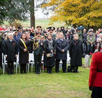A large crowd stands in front of their chairs.  Governor General Julie Payette is standing center, in an army uniform, and salutes.