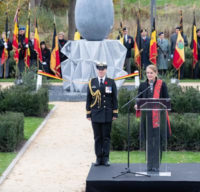 The Governor General of Canada is speaking at a podium, with her female Aide-de-camp on her right side. A giant concret sculpture in the shape of a teardrop is behind her.