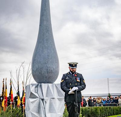 A serviceman stands in front of a monument, eyes towards the ground.  The monument's base has an angular triangle pattern, the top is the shape of a large teardrop.