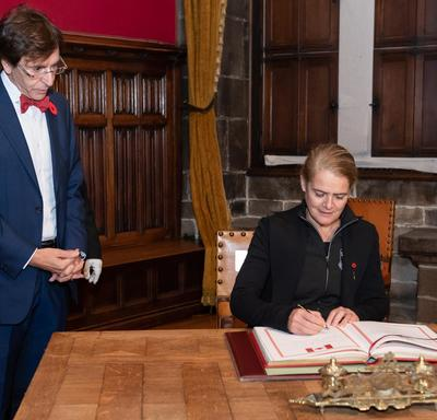 The Governor General is signing a guestbook. The Mayor of Mons, Elio di Rupo, is standing at her right is watching her.