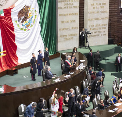 His Excellency Andrés Manuel López Obrador is standing on a stage addressing the members of congress and guests.