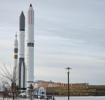 Three rockets are photographed outdoors.  Bottom right, large sign reads 'The National Space Center'.