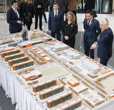 The Governor General is looking at a miniature model on a large rectangular table. A gentleman on her left is explaining the model as he points to it.  They are accompanied by half a dozen other people.