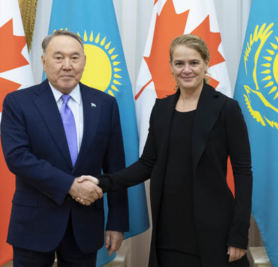 The Governor General shakes the hand of His Excellency Nursultan Nazarbayev, President of Kazakhstan.  They smile for the camera.  Behind them are Canadian and Kazakhstani flags.