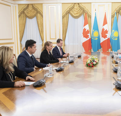A group of 8 people are seated around a large oblong table.  The Governor General, Julie Payette, and His Excellency Nursultan Nazarbayev, President of Kazakhstan are seated in the middle. In the background are Canadian and Kazakhstani flags.