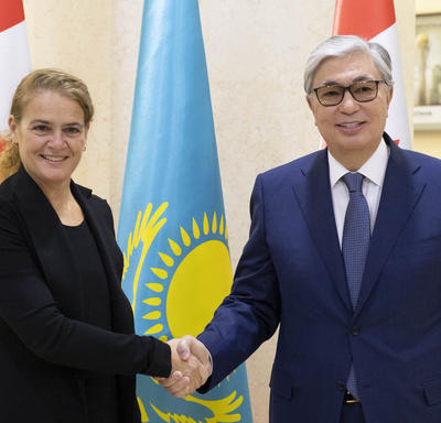 The Governor General shakes the hand of His Excellency Kassym-Jomart Tokayev, Chairman of the Senate of the Parliament of the Republic of Kazakhstan.  They smile for the camera.  Behind them are Canadian and Kazakhstani flags.