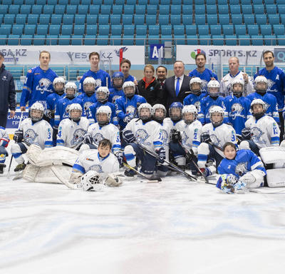 Two youths' hockey teams pose on the ice in an arena. The children are wearing white and blue jersey and full hockey gear. In the background stand adults, including the Governor General, Julie Payette.
