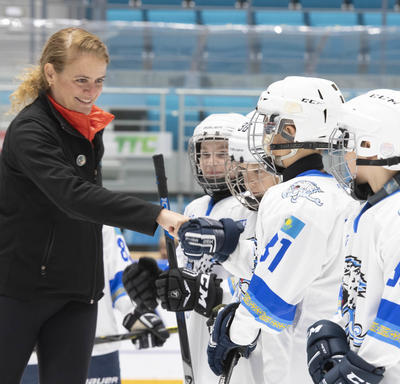 The Governor General, Julie Payette, shakes the hands of children dressed in hockey gear.  They are on the ice in an arena.