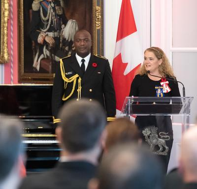 The Governor General stand at a podium and delivers a speech.  Behind her is her Aide-de-Camp in a Navy uniform as well as the Canadian flag.
