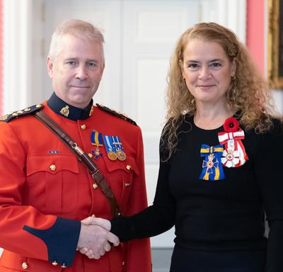 The Governor General stands next to recipient Chief Superintendent Jeffery Joseph Adam who is wearing the Order of Merit of the Police Forces, which he has just received, on his red surge.