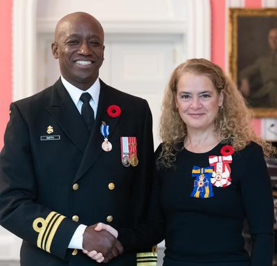 The Governor General stands next to recipient Lieutenant-Commander Paul Anthony Smith who is wearing the Meritorious Service Medal (Military Division) he has just received on his naval uniform.