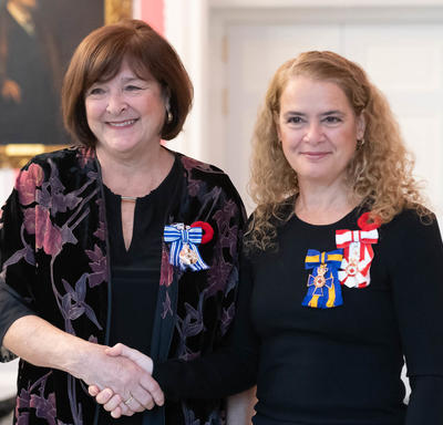 The Governor General stands next to recipient Rachel Corneille Gravel who is wearing the Meritorious Service Medal (Civil Division) she has just received.