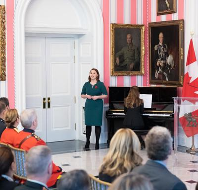 The audience looks on as a Tessa Fackelmann, a local mezzo-soprano, stands next to a piano and signs.  Her accompanist, Danielle Girard, is seated at the piano, back to the audience.