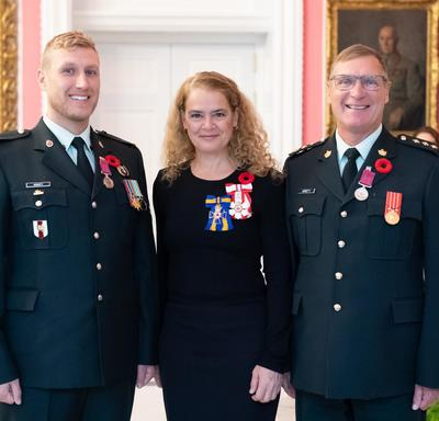 The Governor General stands between Captain Michael Lawrence Kristy (Retired) and Master Corporal Ryan Kristy who are wearing the Medal of Bravery they have just received on their military uniforms.