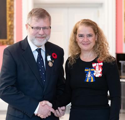The Governor General stands next to recipient Christopher Robert Burn who is wearing the Polar Medal he has just received.