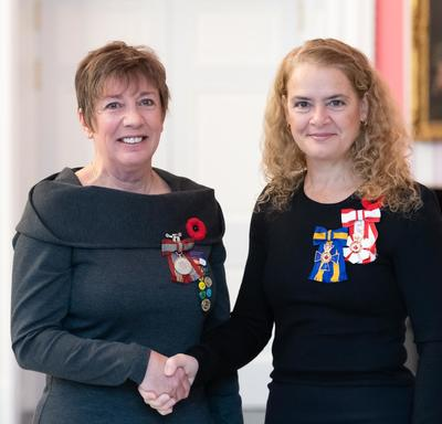 The Governor General stands next to recipient Sara Charron who is wearing the Sovereign's Medal for Volunteers he has just received.