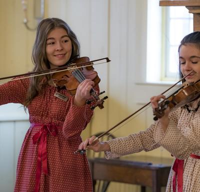 Two women play the fiddle.