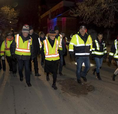 Her Excellency and other volunteers are walking on the street wearing reflective vests.