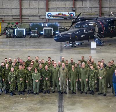 Her Excellency and 17 Wing members are gathered for a group photo.