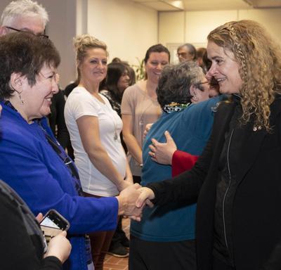 La gouverneure générale, Julie Payette, rencontre des gens dans une foule.  Elle est photographiée en train de serrer la main d'une femme.