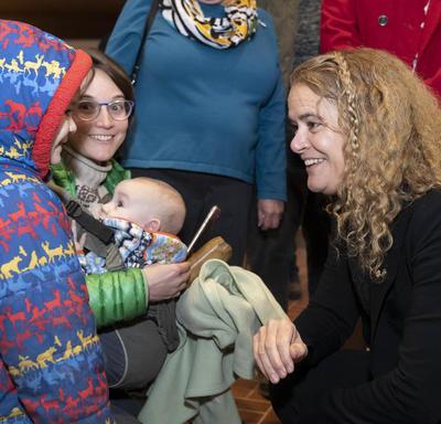 La gouverneure générale, Julie Payette, s'accroupit et parle à un enfant portant un manteau d'hiver.