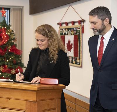 La gouverneure générale signe un livre d'or.  Sandy Silver, premier ministre du Yukon, se tient à ses côtés.