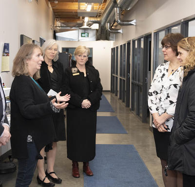The Governor General and Commissionar stand in a hallway and speak to four members of Yukon College.