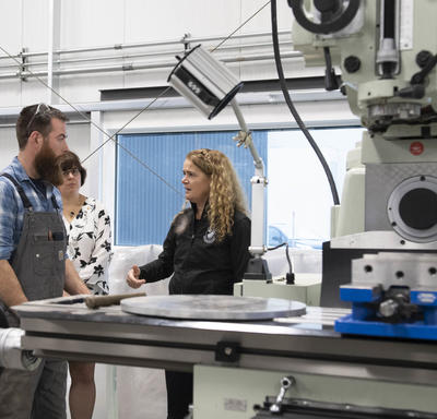 La gouverneure générale se tient près d'une grosse machine métallique.  Elle s'adresse à un membre du Collège du Yukon.