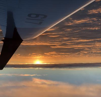 The wing of a plane with the sun setting on the horizon.