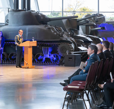 The governor general stands in front of a podium and addresses the crowd, largely in military uniform.  A tank is   behind her, in the background.